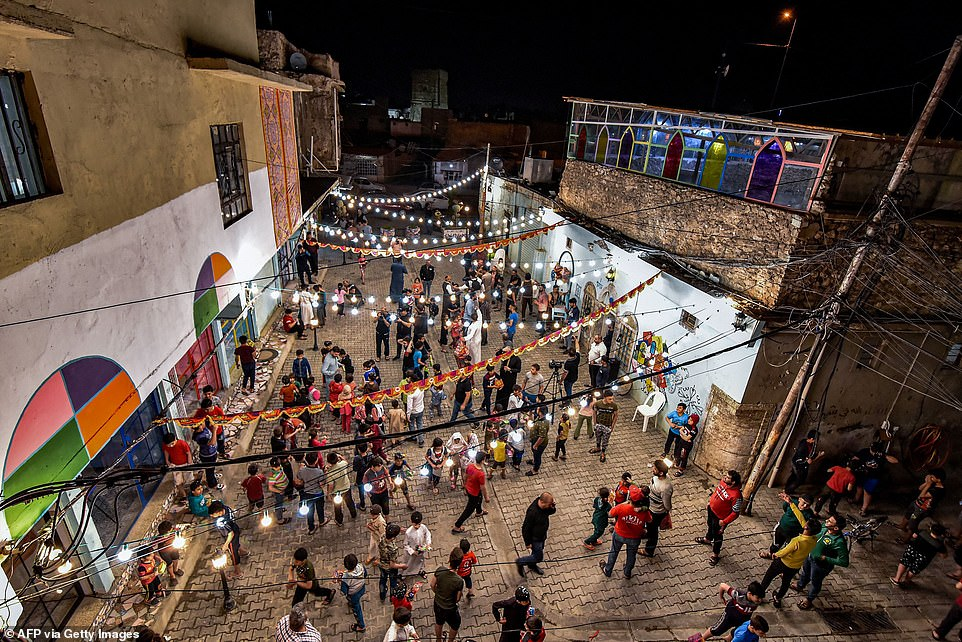 2021: Children in the Iraqi city of Mosul gather along outside on a street to play as part of a celebration for the start of Ramadan hosted by a local cultural NGO