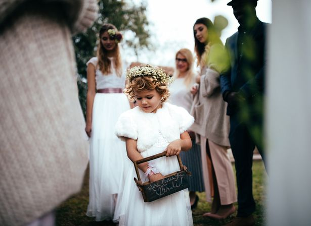 Flower girl holding basket and walking down the aisle with bride at outdoors wedding ceremony