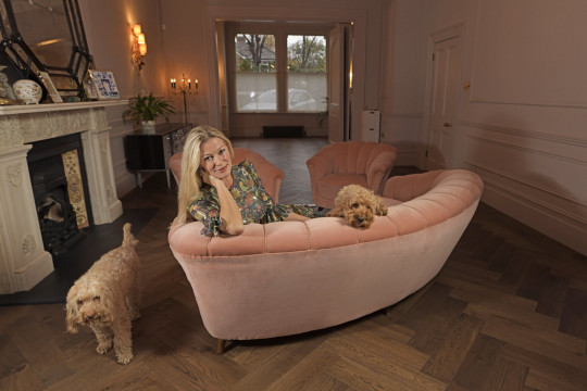 Laura Berkeley-Hawkes on her pink sofa in her ealing home