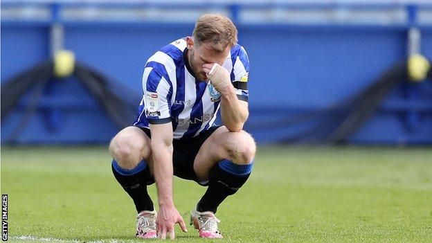 Tom Lees crouches in disappointment after being dispossessed in the lead-up to Jamal Lowe's goal