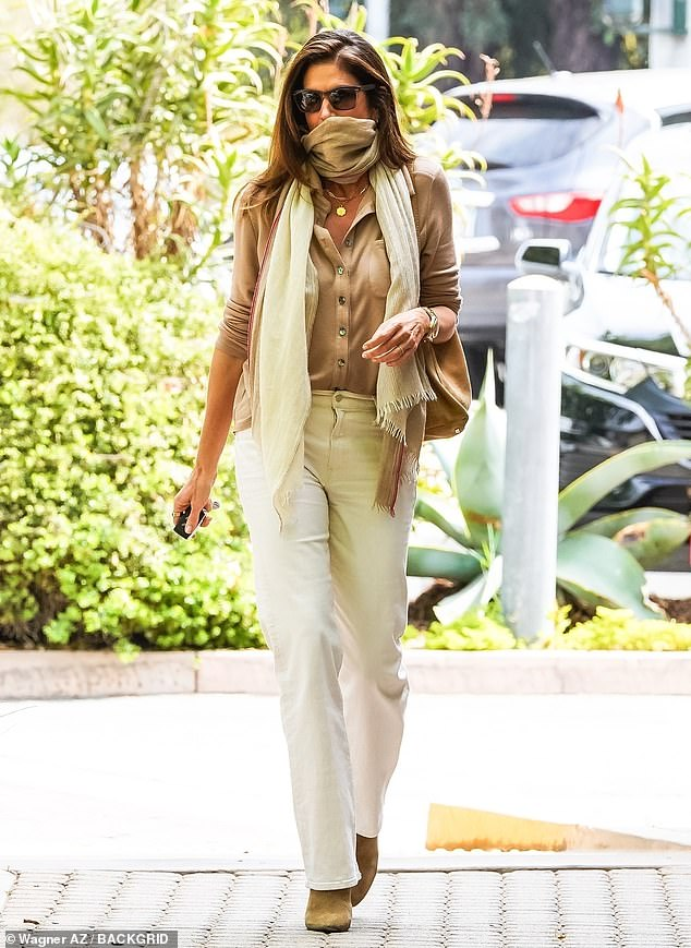 Popping by: She leaned into summer in a pair of white jeans and carried a brown purse over her shoulder while walking to her car