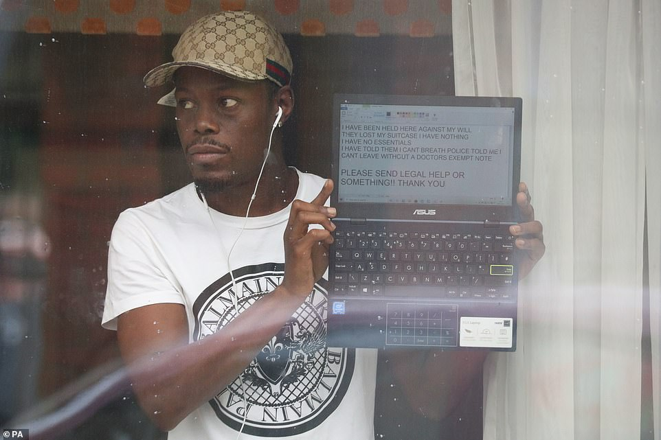 Anthony Pium, 30, from Leyton, East London, holds up his laptop to the window of his room at the Radisson Blu Edwardian hotel near London Heathrow Airport in February, protesting against the mandatory isolation rules