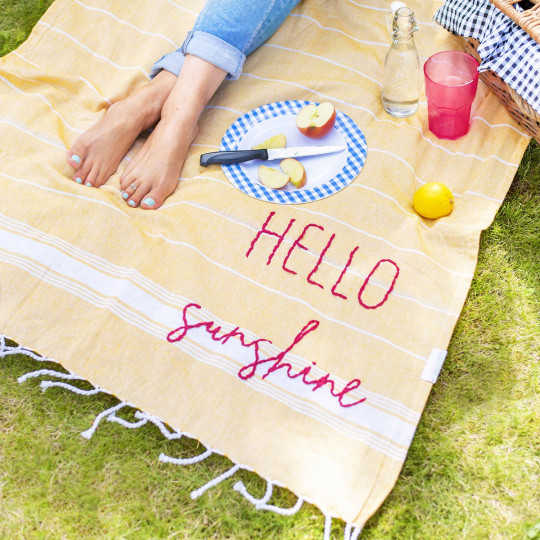 Hand-embroidered cotton picnic blanket by Jonny's Sister = yellow striped picnic blanket with words 'Hello Sunshine'