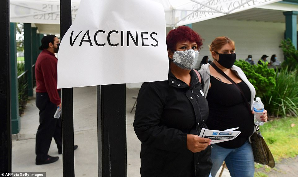 People arrive at a mobile Covid-19 vaccine site in Wilmington district of Los Angeles, California on April 13, 2021, where the Johnson & Johnson Covid-19 vaccine was due to be administered but changed to the Pfizer vaccine following a recommendation from federal health officials. They were given Pfizer or Moderna instead