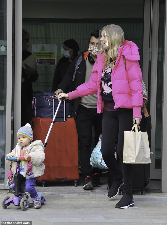 Helping hand: Pasha was seen carrying a number of bags and suitcases during their outing
