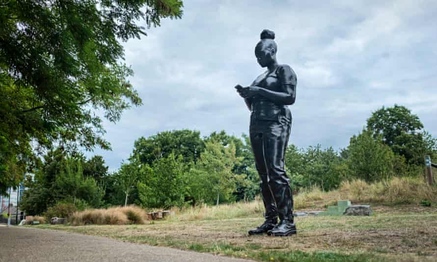Black statue of girl with mobile phone