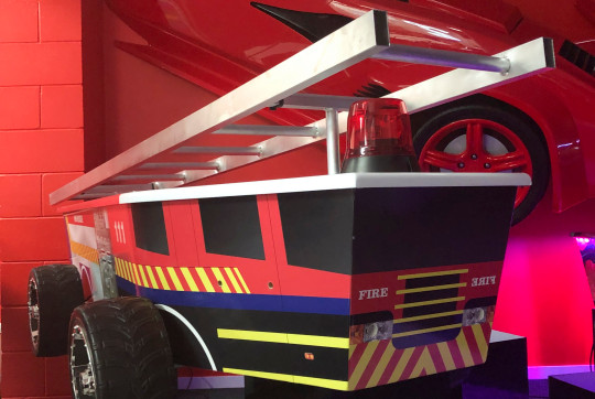 This photo provided by Ross Hall, shows a casket in the design of a fire engine in Auckland, New Zealand Feb. 5, 2019. Auckland company Dying Art makes unique custom caskets which reflect the people who will eventually lay inside them, whether it's a love for fire engines, a cream doughnut or Lego. (Ross Hall via AP)