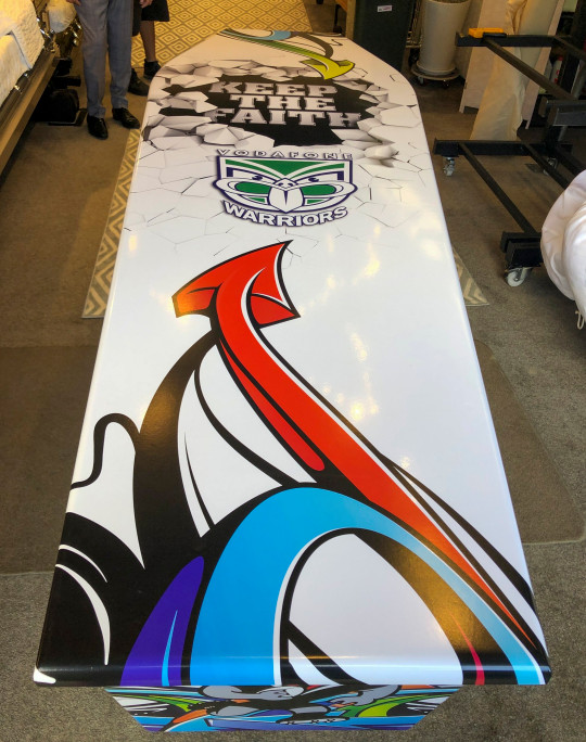 This photo provided by Ross Hall, shows a casket in the colors of the New Zealand Warriors rugby league team in Auckland, New Zealand June 15, 2019. Auckland company Dying Art makes unique custom caskets which reflect the people who will eventually lay inside them, whether it's a love for fire engines, a cream doughnut or Lego. (Ross Hall via AP)
