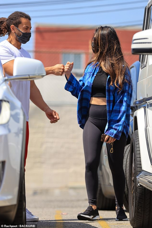 Fist bump! The X-Men star layered on an unbuttoned blue plaid long-sleeved top for a pop of color; seen with her trainer