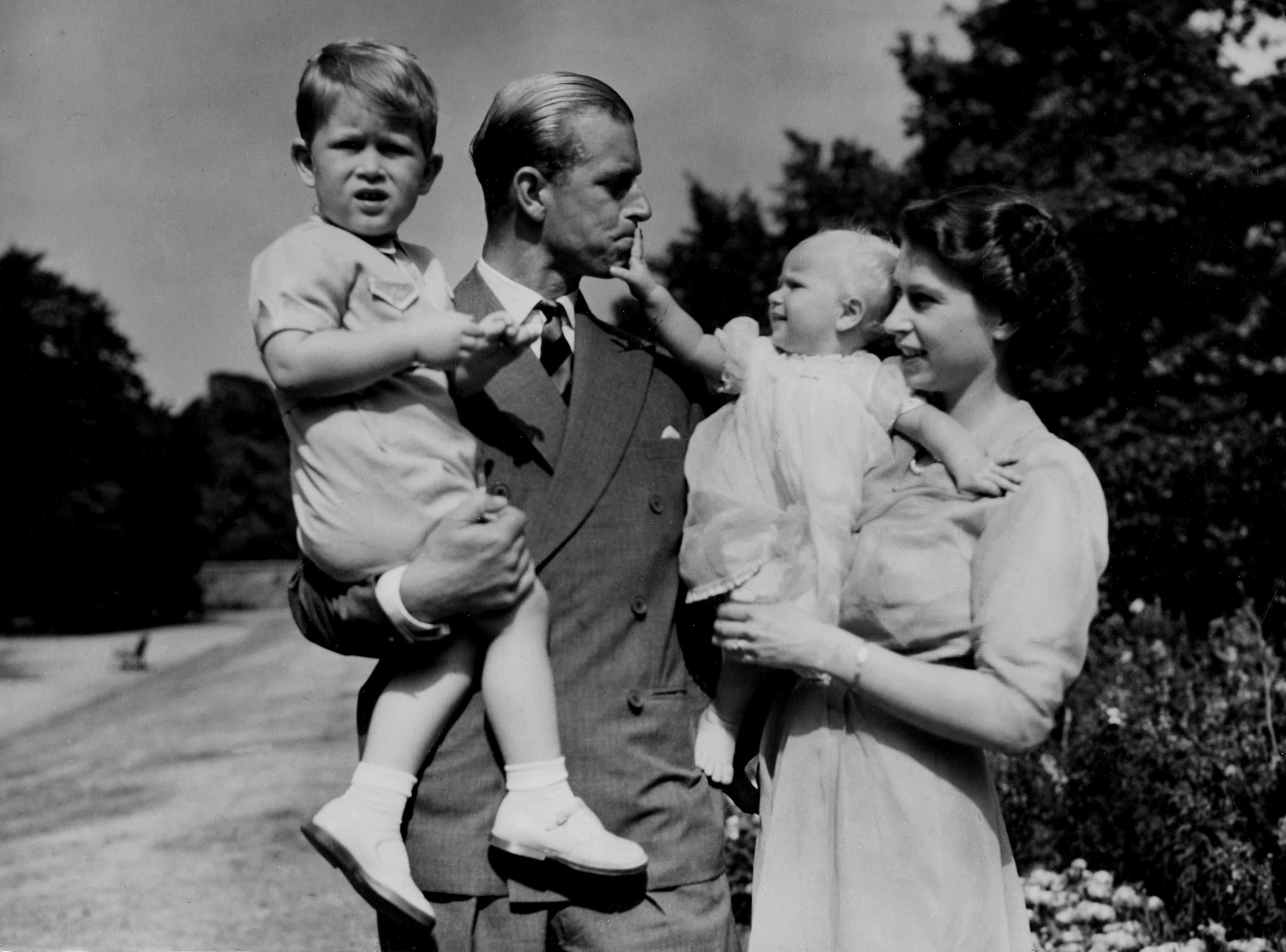 In this August 1951 file photo, the then Princess Elizabeth stands with her husband Philip, Duke of Edinburgh, and their children Prince Charles and Princess Anne at Clarence House, at that point the royal couple's London residence.