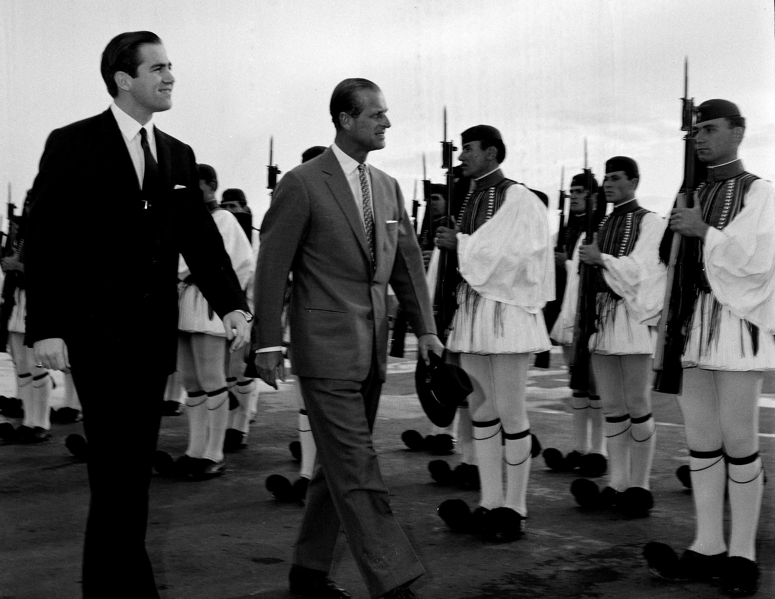 In this March 25, 1965 file photo, King Constantine II of Greece, left, and Prince Philip of Britain review an honour guard of the Greek Royal Evzones Guard as the prince arrives at the Athens Airport for a brief visit as the guest of the Greek royal family.