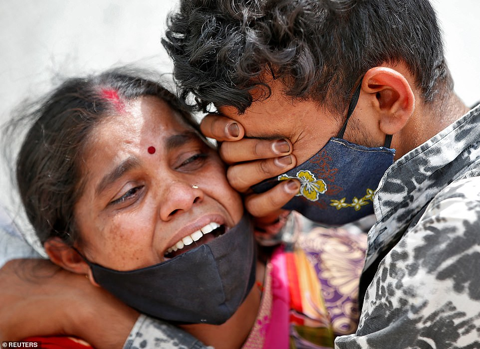 A woman mourns with her son after her husband died due to the coronavirus disease outside a mortuary of a COVID-19 hospital in Ahmedabad