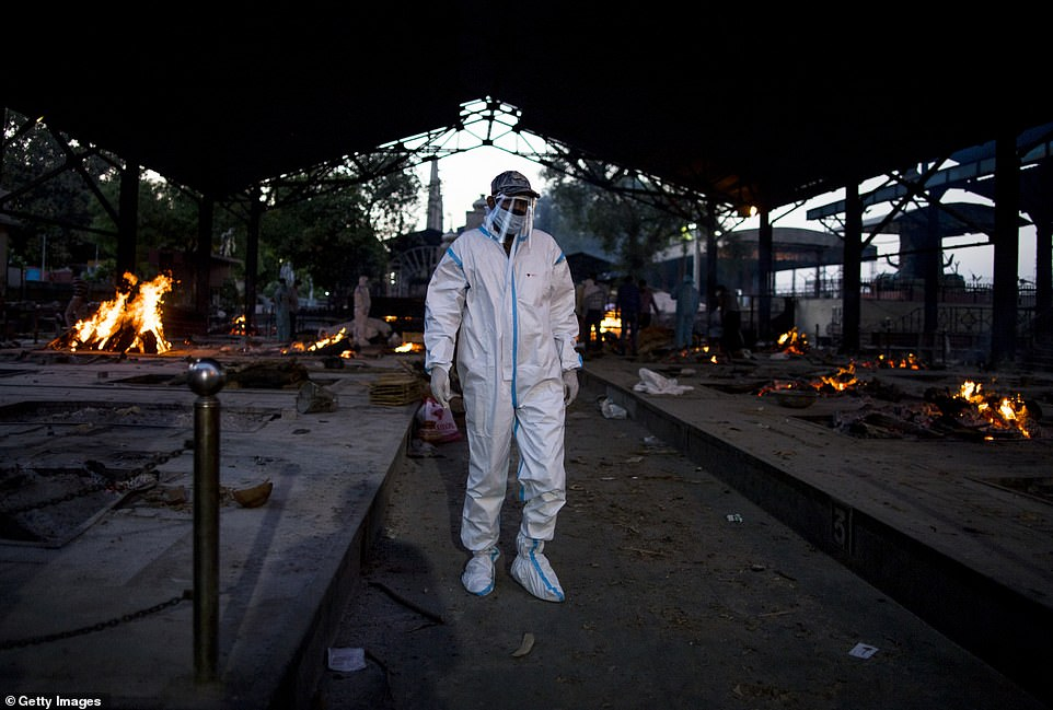 A man in full PPE prepares to perform the last rites of his relative near multiple burning pyres of patients who died of the Covid-19 in Delhi