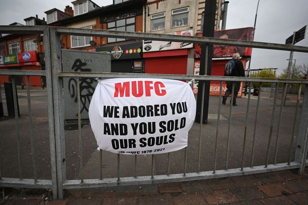 A banner against the proposed European Super League hangs from railings close to Manchester United's Old Trafford stadium in Manchester, northwest England on April 21, 2021.