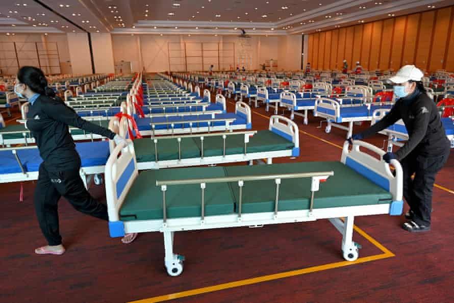 Military personnel prepare beds for Covid patients at a wedding party hall turned field hospital in Phnom Penh.
