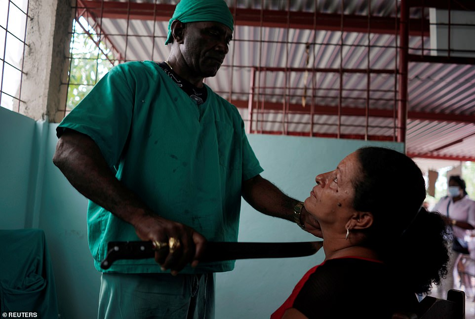 Jorge Goliat performs surgery with a machete and tells his patients drinking half a bottle of rum a week will stop them getting Covid-19