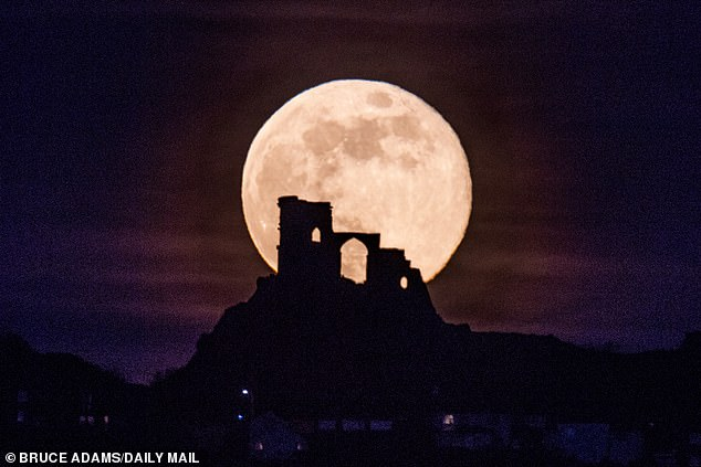 A rare full moon is set to appear in the night sky Monday, April 26 that will be one of the brightest and biggest this year. Pictured is the Pink Moon captured in 2019 behind Mow Cop Castle on the Cheshire/Staffordshire border.