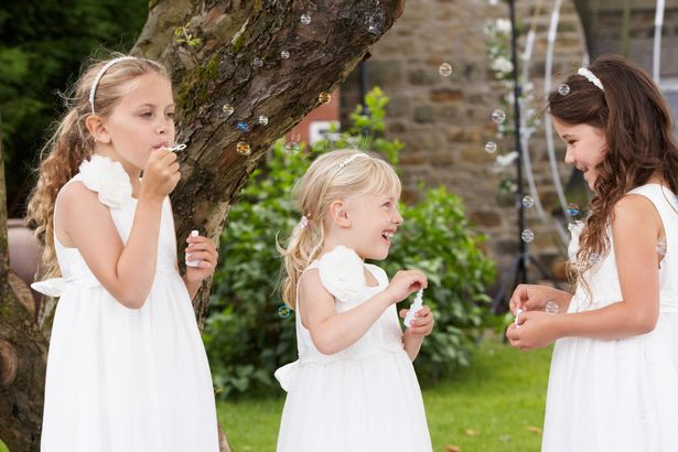 Group of young bridesmaids blowing bubbles