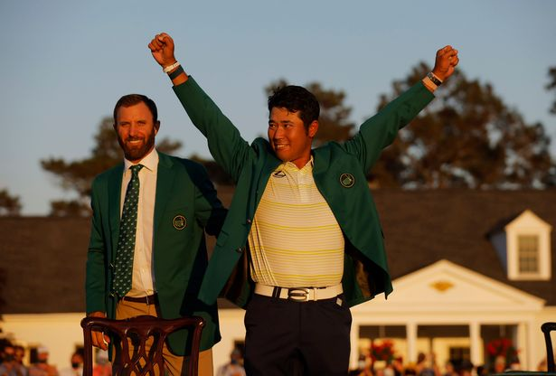 Hideki Matsuyama celebrates with his green jacket after winning The Masters as previous winner Dustin Johnson looks on