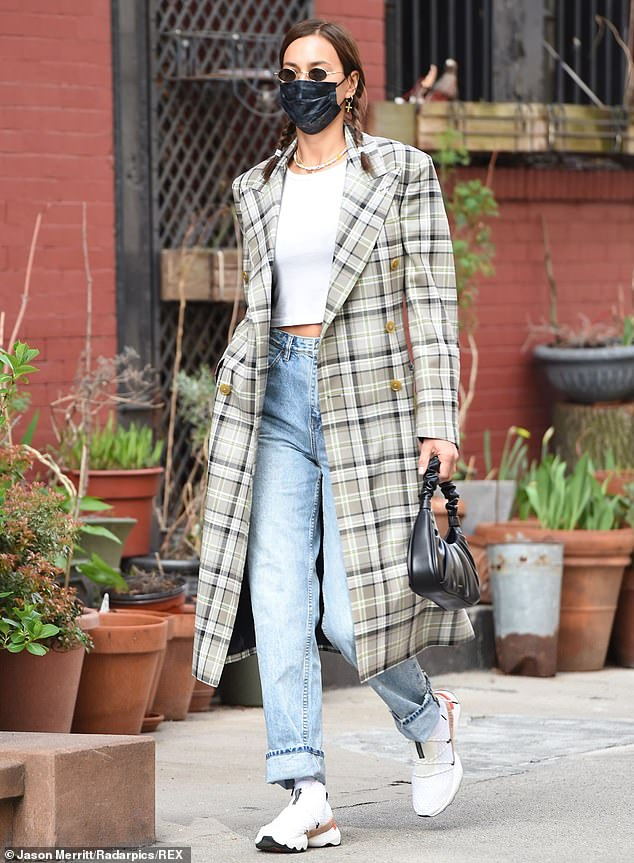 Youthful: Irina Shayk, 35, sports girlish braids and a plaid trench coat while strutting her stuff in NYC