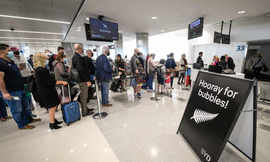 Passengers wearing face masks wait to board Qantas flight QF143 bound for Auckland at Sydney's Kingsford Smith Airport