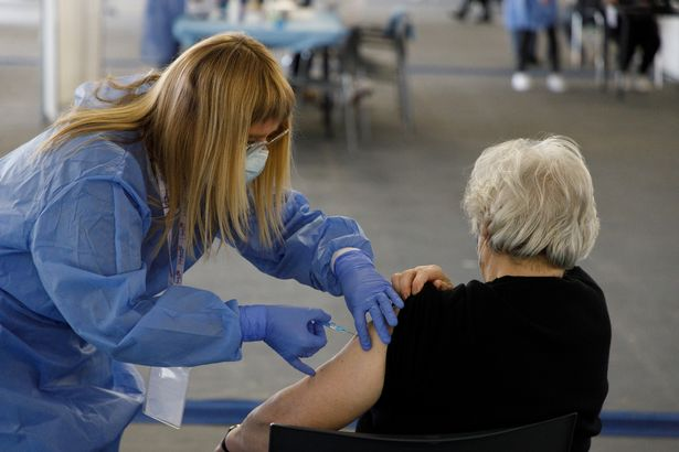 A woman receives a dose of the AstraZeneca vaccine