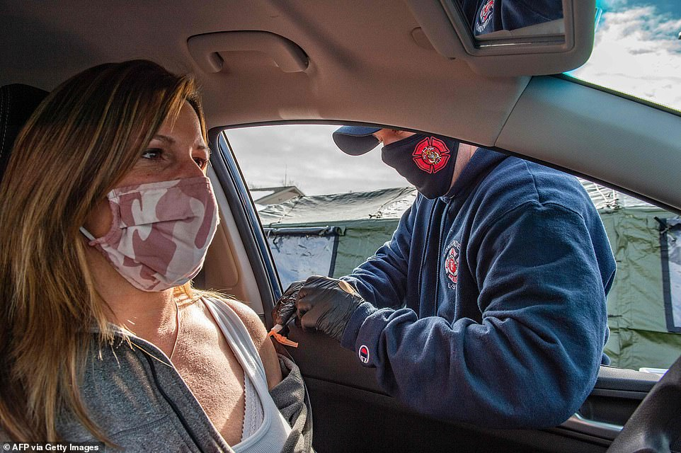 New Hampshire is opening up coronavirus vaccine appointments to out-of-state residents as 42.4% have received at least one dose, one of the highest rates in the U.S. Pictured:A first responder vaccinates a woman in her car at a vaccination center in Londonderry, New Hampshire, February 4