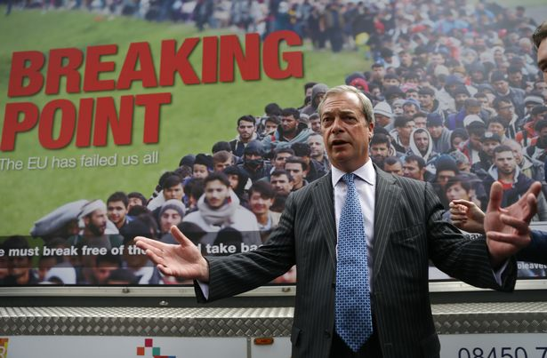 """Nigel Farage standing in front of a """"Breaking Point"""" poster"""