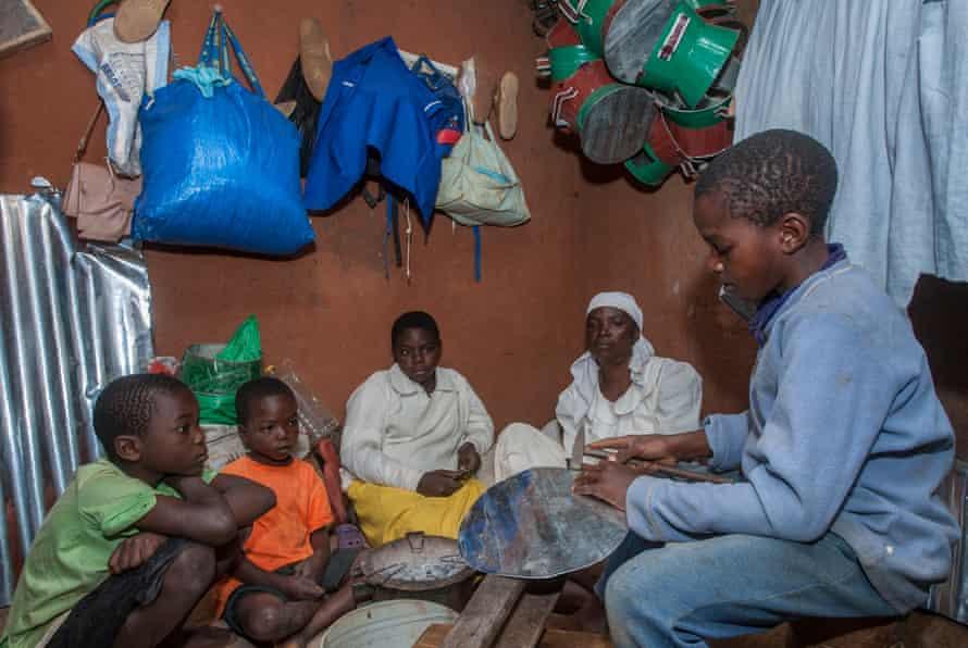 Gift Phiri makes charcoal stoves at his grandmother Rachel Banda's house