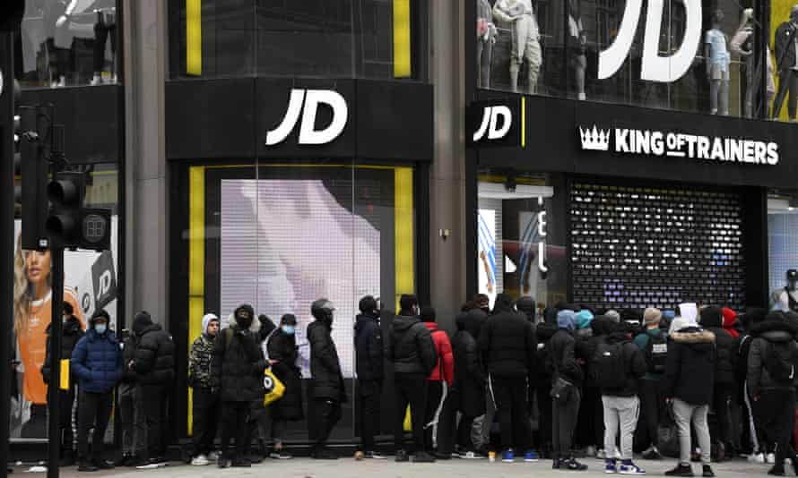 People waiting to buy trainers queue outside JD Sports in Oxford Street in London