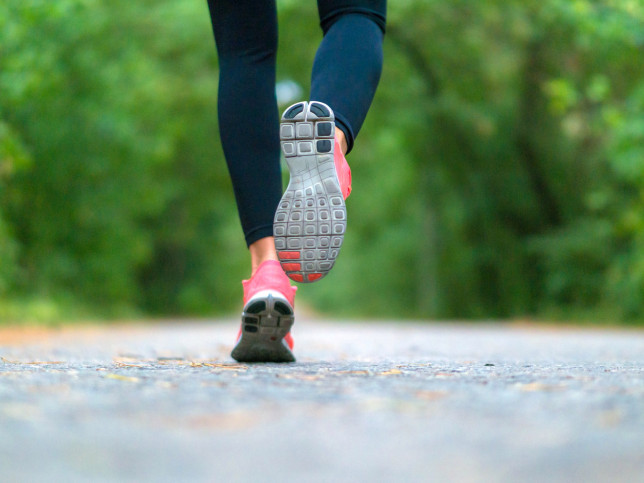 Running woman in the forest. Close-up of sneakers. Healthy lifestyle concept.