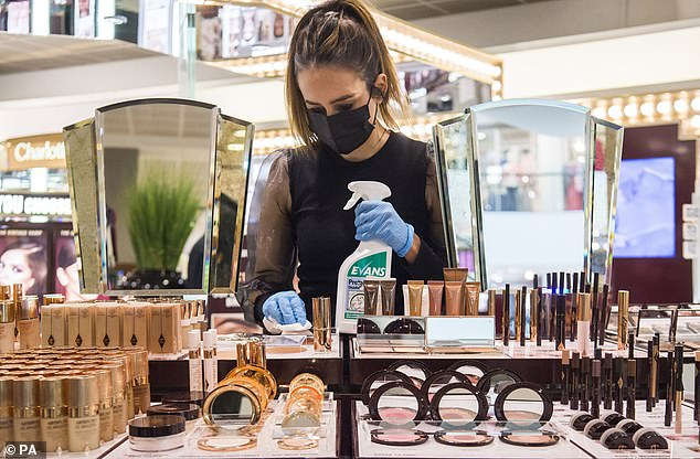 A John Lewis partner cleans the Charlotte Tilbury counter at the Peter Jones store in Sloane Square, Chelsea, London