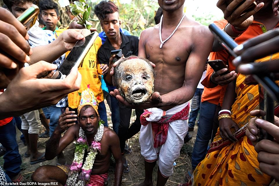 Give a god a bone: A group of worshippers took to the streets inBardhaman, India, today as part of the Gajan Festival, carrying human skulls along as part of the procession