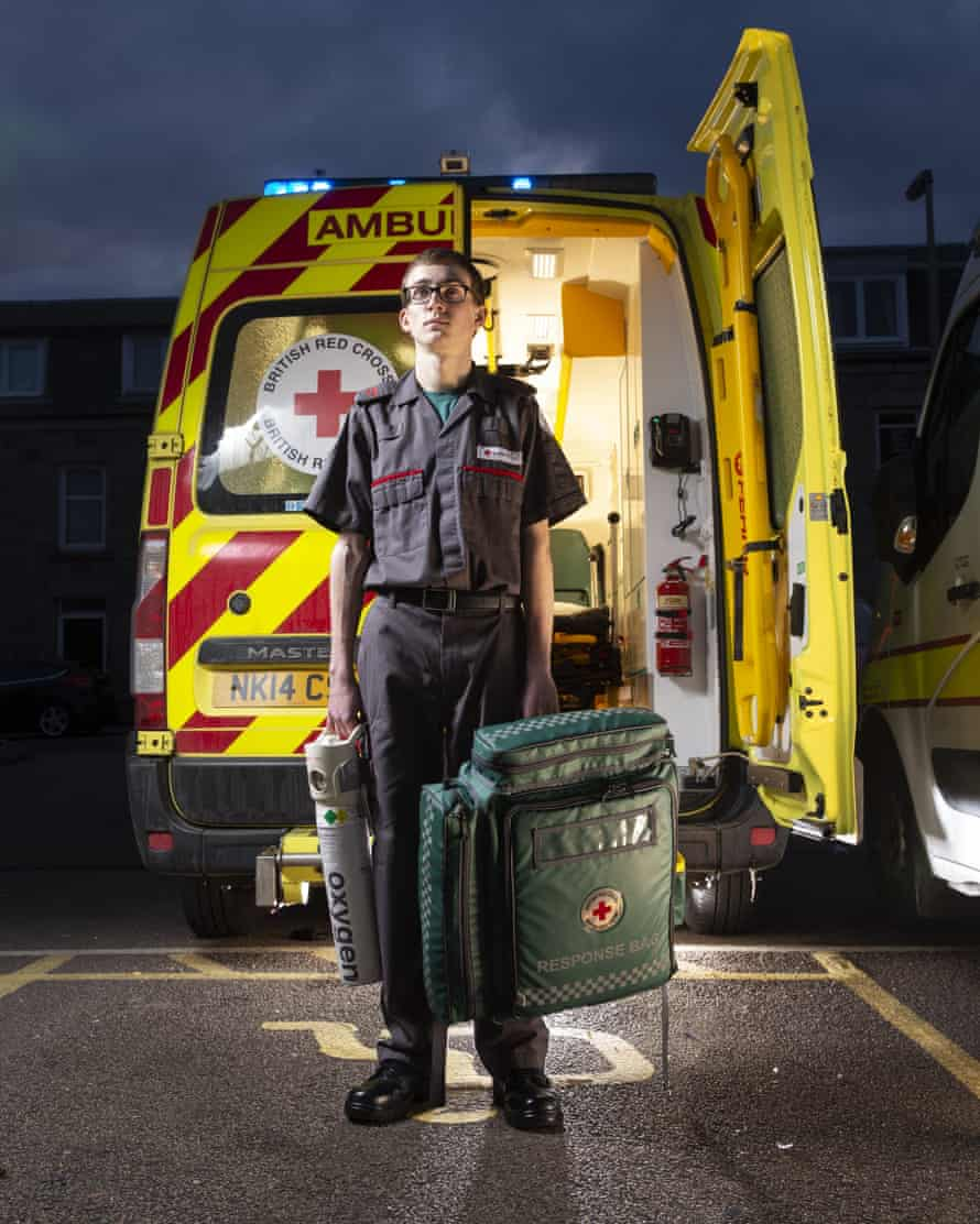 Calum Leitch, who had a place to read medicine, but after volunteering with the Red Cross has decided to become a paramedic, standing by the back of an ambulance holding a medical bag and an oxygen cylinder
