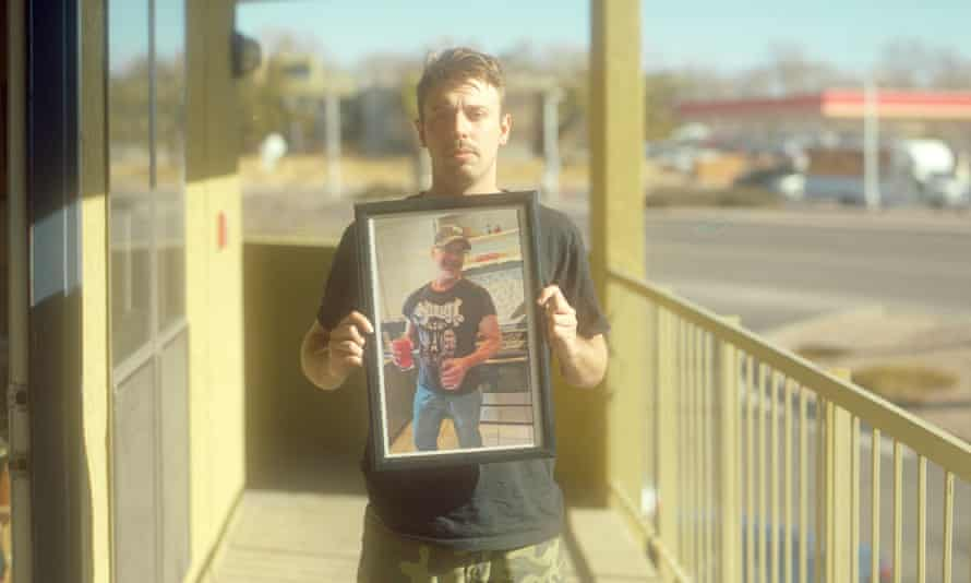 Devon Reiss holds a portrait of his father, Kenneth Reiss, outside of his apartment.