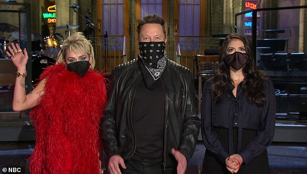Hmm...Miley wore a vast red boa with a black face mask, while Strong wore a black silk outfit with a bow