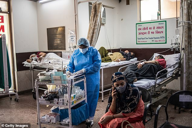 Medics wearing PPE attend to Covid patients on the emergency ward of a hospital in Delhi amid the country's brutal second wave of virus