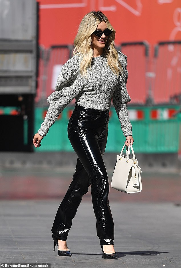 Stylish: Ashley paired the PVC trousers with an eye catching pale green leg-of-mutton sleeve top to complete the workwear look