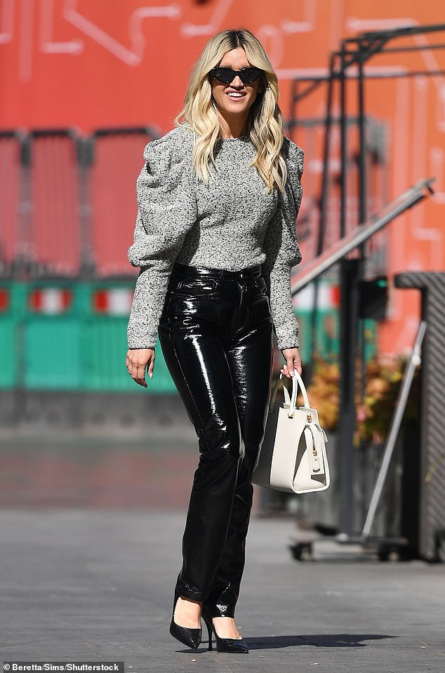 Glamorous: The blonde bombshell wore her tresses in loose waves that cascaded around her shoulders as she strolled through the city in the chic ensemble