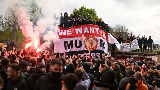 Supporters protest against Manchester United's owners, outside English Premier League club Manchester United's Old Trafford stadium in Manchester, north west England on May 2, 2021, ahead of their English Premier League fixture against Liverpool. - Manchester United were one of six Premier League teams to sign up to the breakaway European Super League tournament. But just 48 hours later the Super League collapsed as United and the rest of the English clubs pulled out.