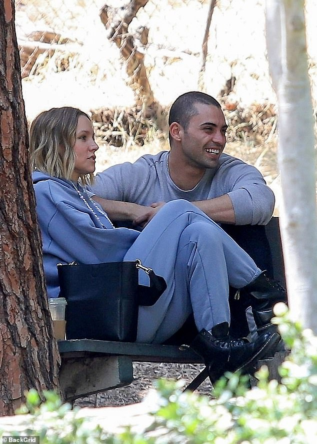 Sharing a laugh: Their afternoon appeared light-hearted as the Filthy Rich star, 29, toted a large bag with their food and smiled at Bell as they made their way to a tree-shaded spot