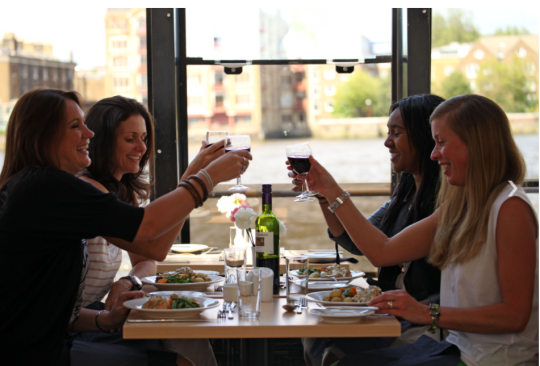 Group of women enjoying wine at a dinner table on a River Thames cruise