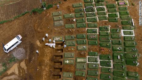 Workers bury a coffin containing the body of a Covid-19 victim at a cemetery reserved for coronavirus deaths in North Sumatra, Indonesia.