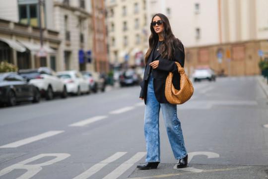 woman street style wearing black blazer with blue jeans