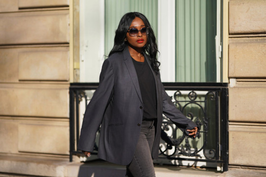 Carrole Sagba @linaose wears sunglasses, a gray oversized blazer jacket from Mugler, a black t-shirt from Calvin Klein, gray denim jeans from Levi's, on February 28, 2021 in Paris, France.