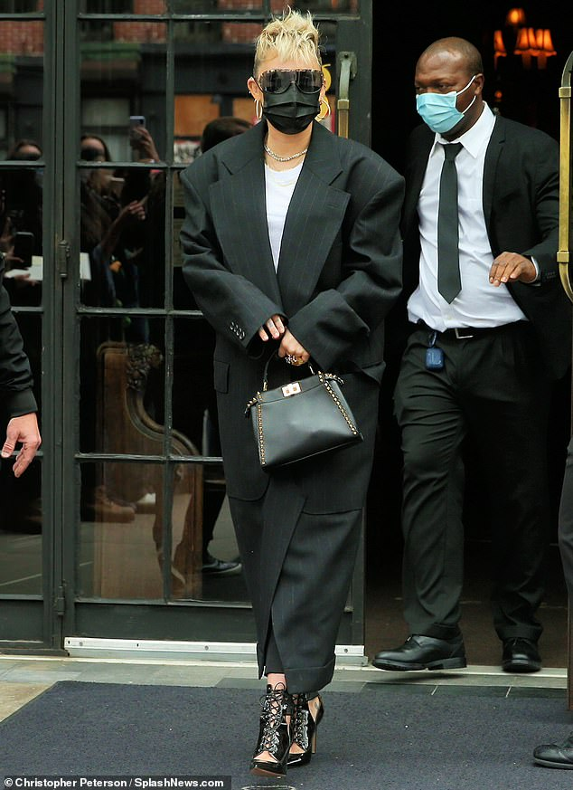 New hair: Miley sported a massive floor-length black coat as she exited the trendy Bowery Hotel, and styled her hair into an edgy blonde mohawk