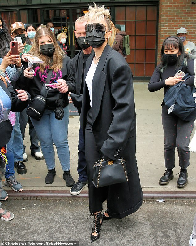 Accessories: She carried a small black studded purse as she made her way through the crowd of fans waiting for her to make an appearance, andkept her face hidden behind a large pair of shades as well as a black face mask to remain safe from the ongoing Covid-19 pandemic