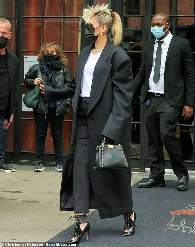 Stylish: She paired the stylish look with a white t-shirt and grey pants, which were cut at the ankle to perfectly display her black peekaboo heels. The Prisoner performer accessorized with a pair of hoop earrings and a silver chain around her neck