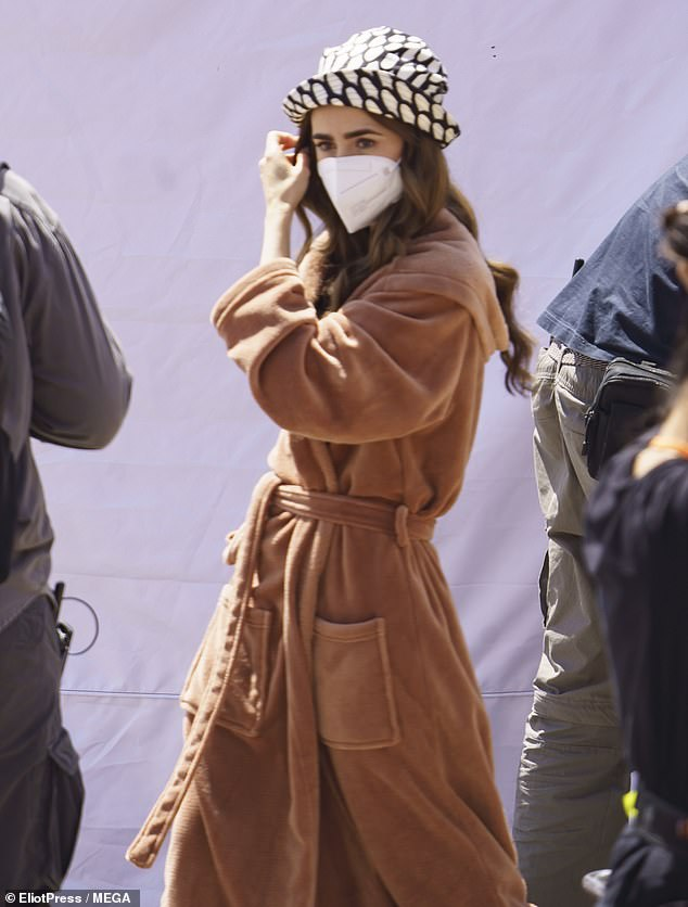 Covered up: The actress later pulled on a stylish tan coloured robe as she made her way across the set