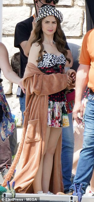 Don't mind me: Sporting a breezy floral minidress, the actress daughter of Genesis star Phil Collins was in high spirits while being readied for her next scene by a group of assistants